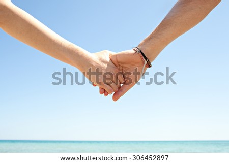 Detail view of a man and a woman hands being held together against a blue sky and sea, on a sunny summer holiday break, outdoors. Tourists holding hands, lifestyle. Honeymoon romance on beach. - stock photo