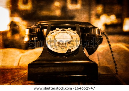 Detail view of old vintage dial telephone on the table, blurred background - stock photo