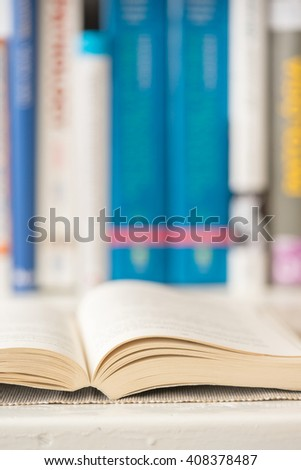Detail view of open book in library. Selective focus. Vertical shot. - stock photo