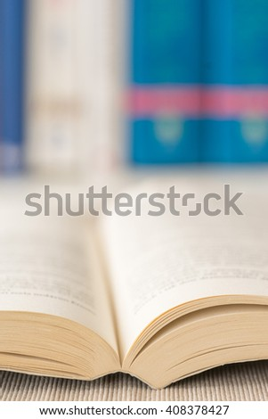 Detail view of open book in library. Shallow depth of field. Vertical shot. - stock photo