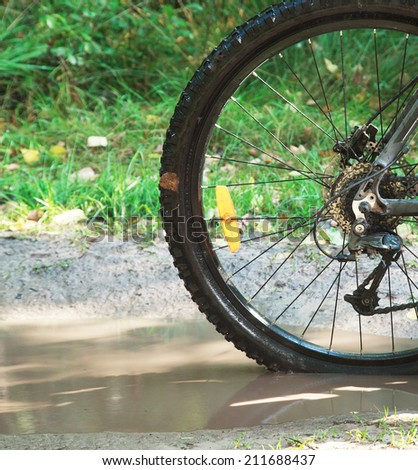 Detail view to the dirty wheel of bicycle in the forest on impassable forest road, cross country offroad  - stock photo