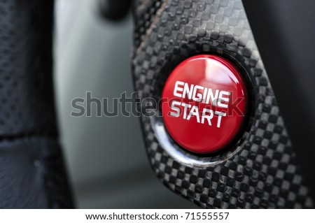Detailed close up of a engine starting button surrounded by carbon fibre - stock photo
