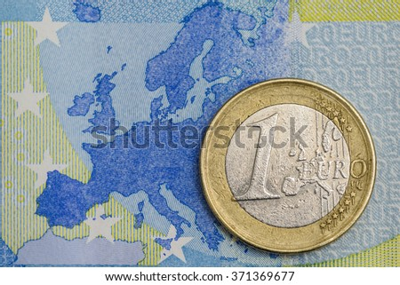Detailed close up of an one euro coin on a blue twenty euro banknote with Europe map in background  - stock photo