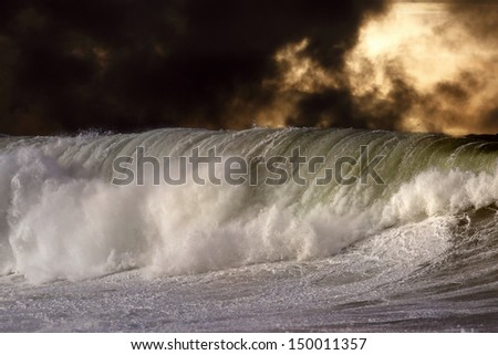 Detailed photo of a big stormy wave crashing over the coast - enhanced sky - stock photo