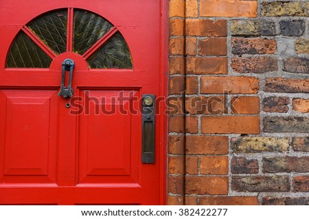 Detailed photo of a red front door and brick wall - stock photo