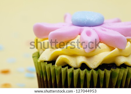 Detailed shot of a colorful cupcake with pink floral pattern. - stock photo