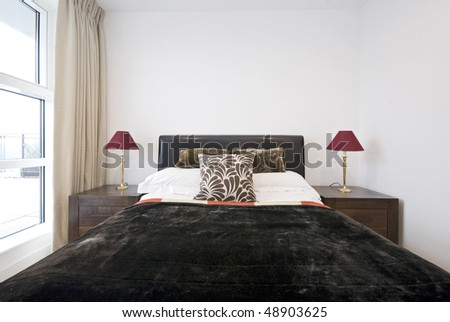 Detailed shot of a modern bedroom with double bed and wooden bedside tables - stock photo