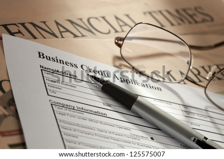 Detailed shot of credit form on newspaper with pen and spectacles. - stock photo