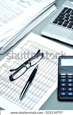 Detailed shot of financial report, ballpoint, glasses, paperwork, laptop and calculator. Can be use as Illustration of financial business, office work, business economy or general business etc. - stock photo