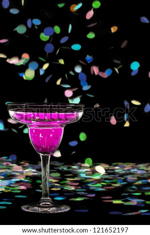 Detailed shot of martini glass with colorful confetti over dark background. - stock photo