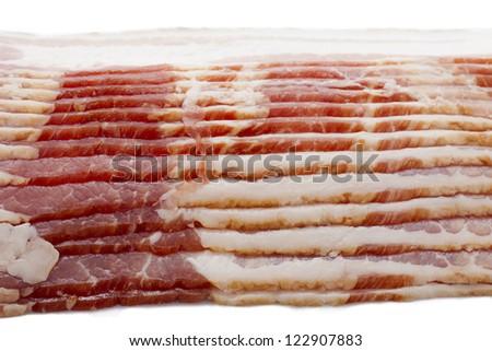Detailed shot of raw bacon displayed on white background. - stock photo