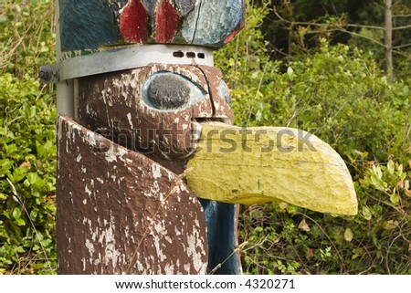 Detailed view of a bird carving on the base of a totem pole at a boy scout camp. The paint is peeling from weathering and age. - stock photo