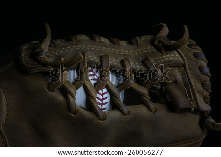 Detailed View of Ball Inside the Webbing of a Baseball Glove - stock photo