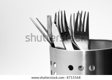 Detailed view on a polished cutlery in aluminum perforated stand isolated on white background - stock photo