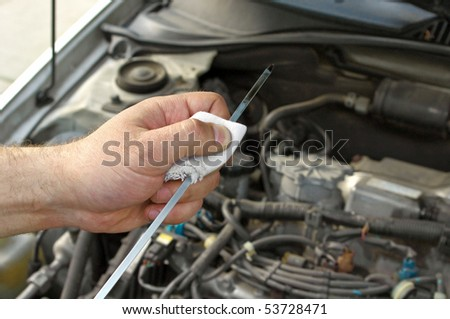 Details checking engine oil dipstick in the car - stock photo