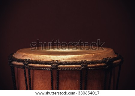 Details of an old wooden djembe, closeup view on ropes, skin and wood.  - stock photo