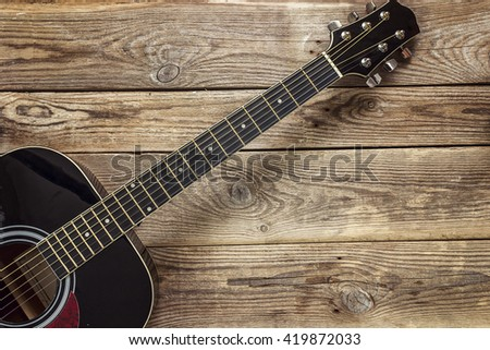 Details of black guitar on the background of old grunge boards. Place for text. Top view - stock photo