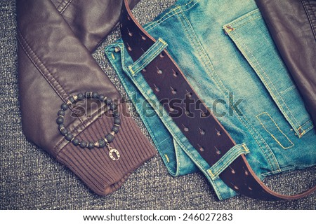 Details of clothes: jeans with a belt, leather jacket, bracelet on the arm. Photo toned in vintage style - stock photo