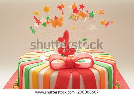 Details of decoration of first year birthday cake, focus on number one.  - stock photo