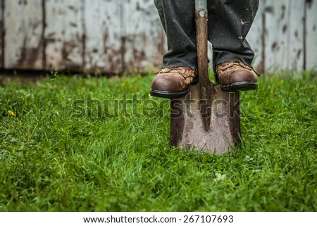 Details of feet and Shovel in front of Barn - stock photo