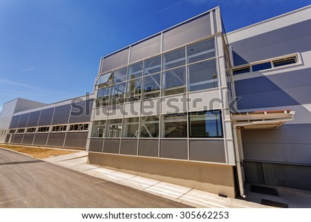 Details of gray facade made of aluminum panels  with doors and windows on industrial building - stock photo