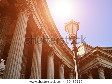 Details of Kazan Cathedral architectural ensemble in Saint Petersburg, Russia - classical colonnade and metal vintage lantern under shining sunset light against blue sky - stock photo