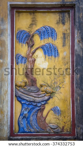 Details of painted reliefs on the side of a gate, showing scenes from nature, in the Imperial City, or Citadel. Hue, Vietnam - stock photo
