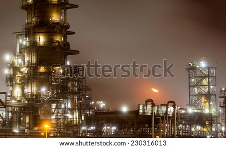 Details of pipes and tanks of a large oil-refinery plant at night - stock photo