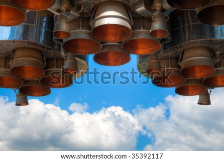 details of space rocket engine against blue sky with clouds - stock photo