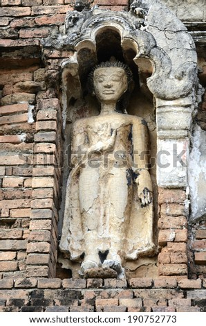 details of the Buddha image in the Ancient Pagoda at  Wat Phra That Hariphunchai, Lamphun Province, Thailand  - stock photo