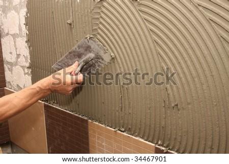 details of trowel spreading mortar for ceramic tile - stock photo