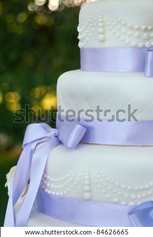 details on a wedding cake with violet ribbons and decorations - stock photo