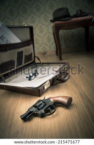 Detective open briefcase with vintage gun on the floor and borsalino hat on background. - stock photo