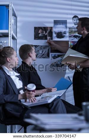 Detective searching files and evidence photos - stock photo