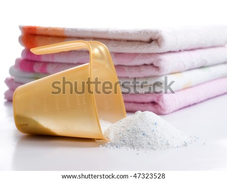 Detergent for washing machine in laundry with towels in the background. - stock photo
