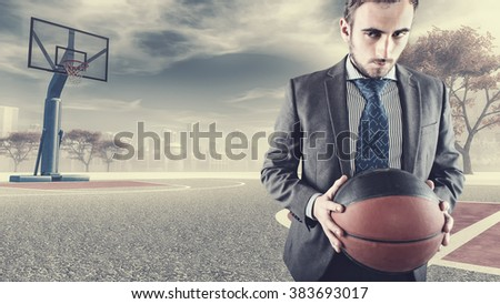 Determinated businessman playing basketball on a plot in the city - stock photo