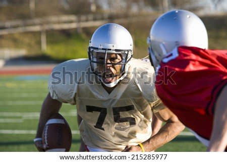 Determined American football player running with ball at opposing players during competitive game, snarling ferociously, front view - stock photo