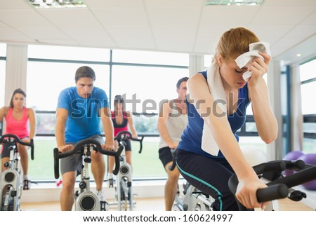 Determined and tired people working out at an exercise bike class in gym - stock photo