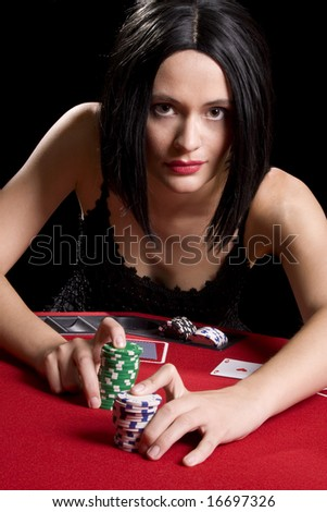 Determined attractive brunette playing cards at a red poker table - stock photo