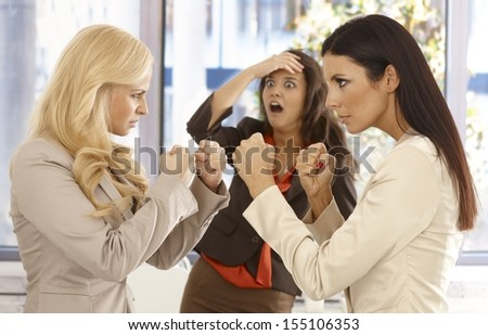 Determined businesswomen fighting at workplace, young colleague watching it with fear from the background. - stock photo