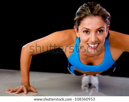 Determined fit woman exercising by doing push-ups - stock photo