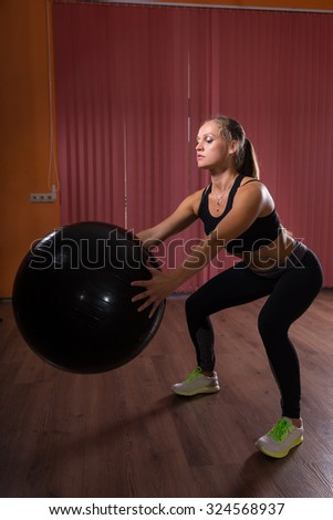 Determined Fit Woman in Squatting Position Holding Exercise Ball Inside a Fitness Studio. - stock photo
