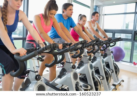 Determined five people working out at exercise bike class in gym - stock photo
