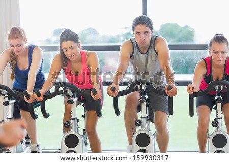 Determined four people working out a class in gym - stock photo