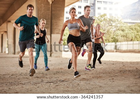 Determined  group of young people running together in city. Running club members training together. - stock photo