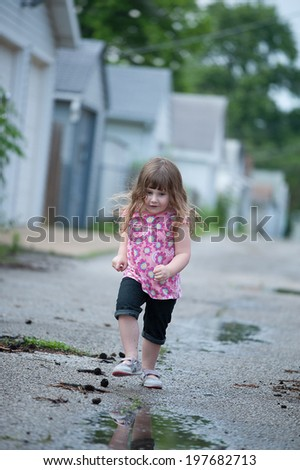 Determined little girl races toward the next puddle in an alley - stock photo