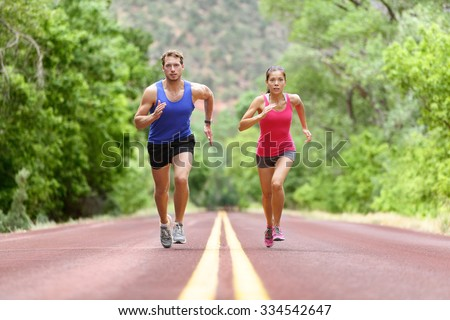 Determined man and woman running on road against trees. Runners sprinting in Full length of sporty male and female are in sports clothing. Athletic runner fitness sport couple are exercising outside. - stock photo