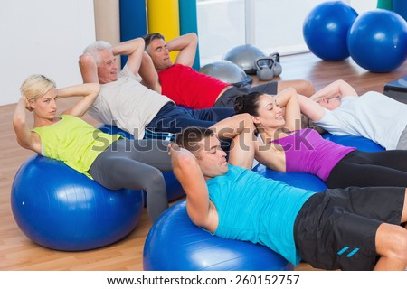 Determined people stretching on exercise balls in fitness club - stock photo