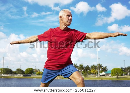 Determined senior man doing yoga warrior pose at lakeshore - stock photo