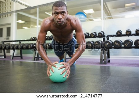 Determined shirtless muscular man doing push ups with ball in the gym - stock photo